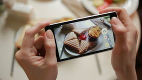 Trendy man in a restaurant make photo of food with mobile phone camera. sandwich stock footage