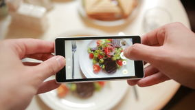 Trendy man in a restaurant make photo of food with mobile phone camera. stock video footage
