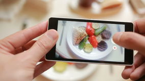 Trendy man in a restaurant make photo of food with mobile phone camera stock video