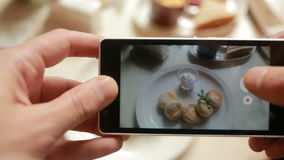 Trendy man in a restaurant make photo of food with mobile phone camera stock video footage