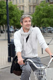 Trendy man riding bike in the city Stock Images