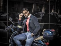 Trendy man by scooter in city Stock Photos