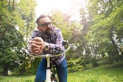 Trendy man sitting on bike looking away Royalty Free Stock Photo