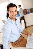 Trendy man sitting on desk in office Royalty Free Stock Image
