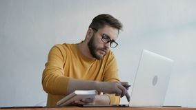 Trendy man takes notes in a notebook at the office. One handsome caucasian employee with glasses working at wooden table with monitor of pc near white wall stock video