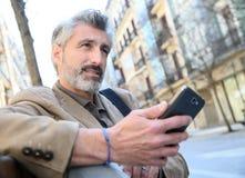 Trendy mature man using smartphone Stock Images