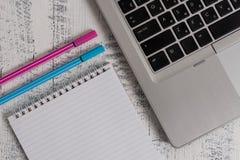Trendy metallic laptop ruled spiral notepad pens lying wooden rustic vintage table. Personal computer timber desktop. Metallic laptop blank ruled notepad pens stock photo