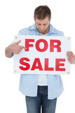 Trendy model holding a for sale sign and looking at it Royalty Free Stock Photo