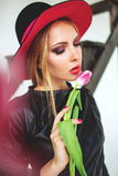 Trendy model in leather black dress and hat with flowers Royalty Free Stock Image
