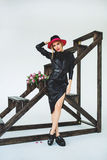 Trendy model in leather black dress and hat with flowers Stock Photos