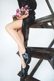 Trendy model in leather black dress and hat with flowers Royalty Free Stock Photos