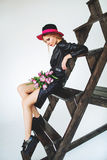 Trendy model in leather black dress and hat with flowers Royalty Free Stock Images