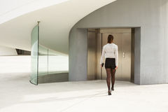 Trendy modern businesswoman entering corporate building. Trendy young businesswoman about to enter in modern corporate building elevator on a working day Stock Images
