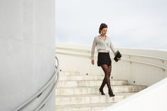 Trendy modern businesswoman walking down stairs. Trendy young businesswoman walking down the stairs of corporate building on a working day. Brunette professional Royalty Free Stock Image