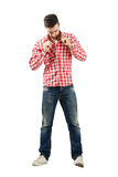 Trendy modern guy buttoning plaid shirt Royalty Free Stock Images