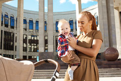Trendy modern mother on a city street with a pram. Young mother Stock Photography