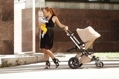 Trendy modern mother on a city street with a pram. Young mother Stock Image