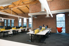 Trendy modern open concept loft office space with big windows, natural light and a layout to encourage collaboration. View of a trendy modern open concept loft stock photo