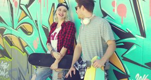 Trendy modern urban couple chatting at skate park. Trendy modern urban couple chatting at a skate park standing leaning against a colorful graffiti covered wall stock footage