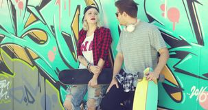 Trendy modern urban couple chatting at skate park. Trendy modern urban couple chatting at a skate park standing leaning against a colorful graffiti covered wall stock video footage