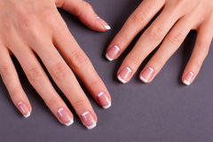 Trendy moon french manicure. Trendy moon french manicure on a grey background royalty free stock photo