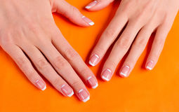Trendy moon french manicure. Trendy moon french manicure on an orange background stock photography