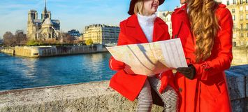 Trendy mother and daughter travellers in Paris, France with map. Bright in Paris. trendy mother and daughter travellers in red coats on embankment near Notre Royalty Free Stock Photography
