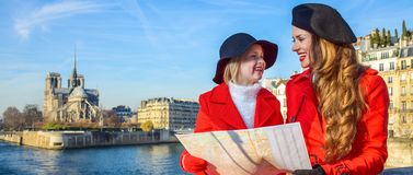 Trendy mother and daughter travellers in Paris, France with map Stock Photo
