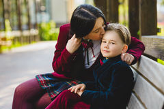 Trendy mother kissing her stylish son outdoor Royalty Free Stock Photography
