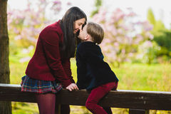 Trendy mother kissing her stylish son outdoor Stock Photos