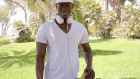 Trendy muscular young man holding a skateboard. Trendy muscular young African man holding a skateboard and wearing headphones round his neck posing in a tropical stock footage