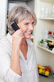 Trendy older woman talking on the phone. Trendy older woman with a lively smile standing in her kitchen talking on the phone Stock Photos