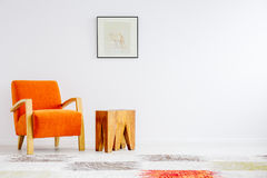 Trendy orange chair. Next to creative coffee table with bright picture above royalty free stock photo