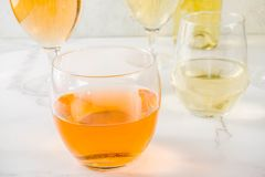 Trendy orange wine. With white wine in different glasses, white concrete background copy space royalty free stock photo