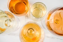 Trendy orange wine. With white wine in different glasses, white concrete background copy space stock photography