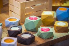 Trendy original wooden candlesticks of geometric shapes of different colors stock images