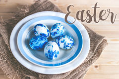 Trendy painted Easter eggs on a plate Stock Image