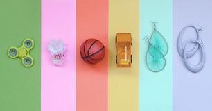 Trendy pastel composition with earrings, sunglasses, beverage can, basketball ball, toy truck, flower and spinner. Trendy fashionable pastel composition with royalty free stock photo