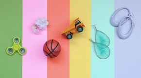 Trendy pastel composition with earrings, sunglasses, beverage can, basketball ball, toy truck, flower and spinner. Trendy fashionable pastel composition with stock photos