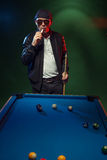 Trendy pool player in a leather jacket and cap Royalty Free Stock Photos