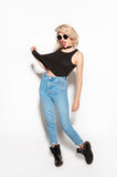 Trendy rebel girl posing. Young stylish rebel girl in sunglasses and casual outfit posing on white backgr Stock Photo