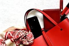 Trendy red feminine handbag spilling objects royalty free stock photos