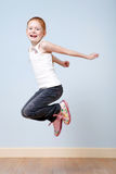 Trendy red-haired girl jumping indoors royalty free stock image