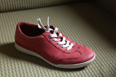 Trendy red sport shoes. On a textile floor Stock Image