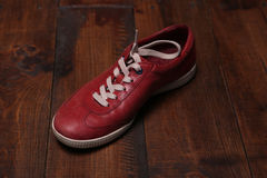 Trendy red sport shoes. On a wooden floor Royalty Free Stock Photography