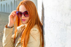 Trendy redhair woman in fashion sunglasses outdoors Stock Images