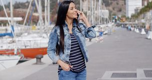 Trendy relaxed young woman talking on a mobile. Trendy relaxed young woman in denim jeans standing outdoors on a promenade talking on a mobile phone with a happy stock video footage