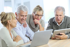 Trendy retired people spending time using tablet Royalty Free Stock Photos