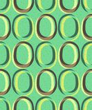 Trendy retro seamless pattern. Pattern in the style of the 60s and 70s. Yellow-brown ovals on a green background Stock Photos