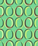 Trendy retro seamless pattern. Pattern in the style of the 60s and 70s. Yellow-brown ovals on a green background Stock Image